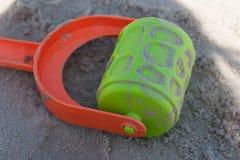 在沙子的绿色和红色玩具 图库摄影