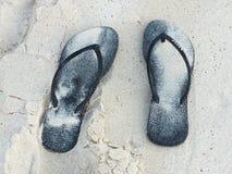 在沙子的黑鞋子 免版税库存照片