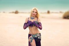 在沙子的Beautidul微笑的夫人跳舞肚皮舞离开 库存照片