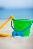 在沙子的Plastik五颜六色的玩具在海滩 免版税库存照片