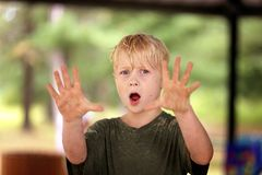 在沙子盖的肮脏的男孩反对和举起手 图库摄影