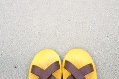 在沙子背景的橙色拖鞋在海边 免版税库存照片