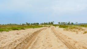 在沙子路的低角度视图在一个朦胧的荒地风景在富兰德 免版税库存照片