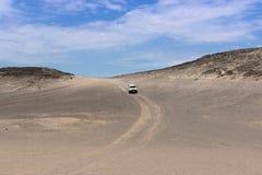 在沙子路的汽车在swakopmund, nam东部的mondlandschaft 库存图片