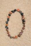 在沙子选择聚焦的小卵石0数字 免版税库存图片