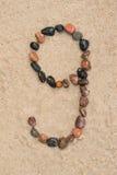 在沙子选择聚焦的小卵石9数字 免版税库存照片