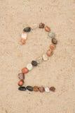 在沙子选择聚焦的小卵石2数字 免版税库存图片