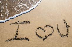在沙子雕刻的爱 免版税库存照片