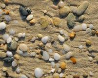 在沙子驱散的大理石小卵石 库存图片