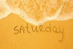 在沙子-写的星期六在海滩纹理 库存照片