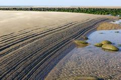 在沙子-在诺瑟姆海滩做的样式的波纹由外出的浪潮,与小卵石和大西洋 免版税库存照片