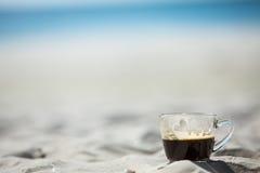 在沙子&海背景的咖啡杯 免版税图库摄影