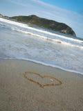 在沙子绘的心脏的被定调子的图象反对海 库存照片