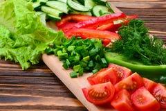 在沙拉的新鲜的被切的菜:萝卜,樱桃,绿色,黄瓜,红辣椒 库存图片