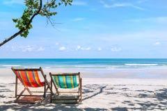 在沙滩的两张海滩睡椅在酸值张Th的海附近 免版税库存图片