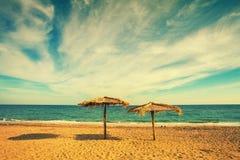 在沙滩的两把秸杆伞 库存照片