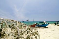 在沙滩的传统渔夫小船 明亮的晴天和蓝天背景 库存图片