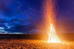 在沙滩的大明亮的篝火在晚上 免版税图库摄影