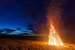 在沙滩的大明亮的篝火在晚上 免版税库存照片