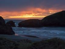在沙滩的日落与海堆 免版税库存照片