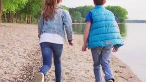 在沙滩的男孩和女孩奔跑沿海岸线 股票录像