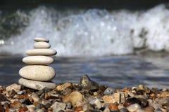 在沙滩的石头与风大浪急的海面 免版税库存图片