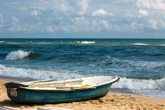 在沙滩的老划艇 刮风的天气,波浪在海 免版税库存图片