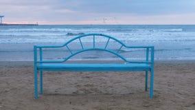 在沙滩的蓝色长凳在日落 放松的方便基础设施由海 失败大浪通知 股票视频