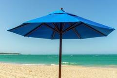 在沙滩的蓝色阳伞 库存照片