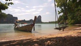 在沙滩附近的长尾巴小船与摇摆 股票录像