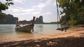 在沙滩附近的长尾巴小船与摇摆 股票视频