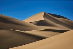 在沙漠、温暖的干燥沙子和蓝天的光滑的沙丘 库存图片