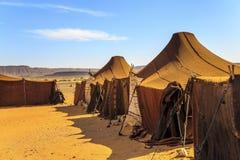 在沙漠中间的帐篷有山的在背景中,在一个晴天 免版税图库摄影