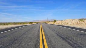 在沙漠中间的空的路有清楚的蓝天的 库存照片
