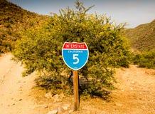 在沙漠刺tr前面的加利福尼亚跨境5交通标志 库存图片