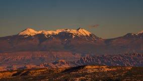 在沙漠和雪加盖的山的日落 免版税库存照片
