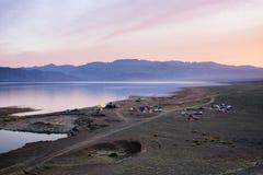 在沙漠山湖旁边的阵营 库存图片