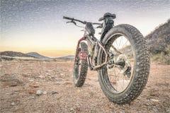 在沙漠山行迹的肥胖自行车 免版税库存图片