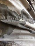 在沙漠战士作战长裤的伪装材料 免版税图库摄影