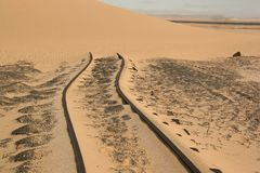 在沙漠沙子的轮胎轨道 免版税库存照片
