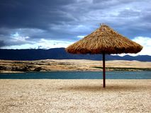 在沙漠海边的沙滩伞 库存图片
