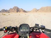 在沙漠种族的方形字体自行车 在沙漠路的所有地形车或quadricycle视图 库存图片