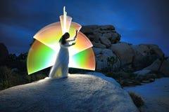在沙漠绘的人光在夜空下 免版税库存图片