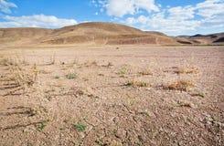 在沙漠谷的距离的山与旱田的在烧焦的太阳下 免版税库存图片