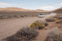 在沙漠路的汽车 免版税库存照片