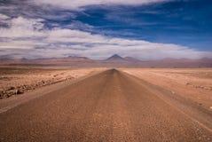 在沙漠风暴期间的阿塔卡马沙漠路与安地斯山在背景,圣佩德罗火山de阿塔卡马,智利中 库存照片