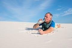 在沙漠水瓶和饮料找到的人贪婪 免版税库存照片