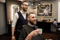 在沙龙的愉快的理发师和顾客饮用的咖啡 库存图片