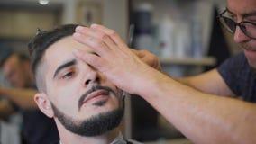 在沙龙的行家发型 专业理发师使用一个普通刀片做胡子趋向形式 影视素材
