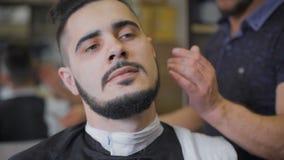 在沙龙的行家发型 专业理发师使用一个普通刀片做胡子趋向形式 股票录像